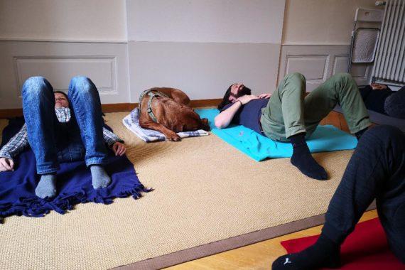 des gens et un chien couché confortablement sur le sol avec la Technique Alexander