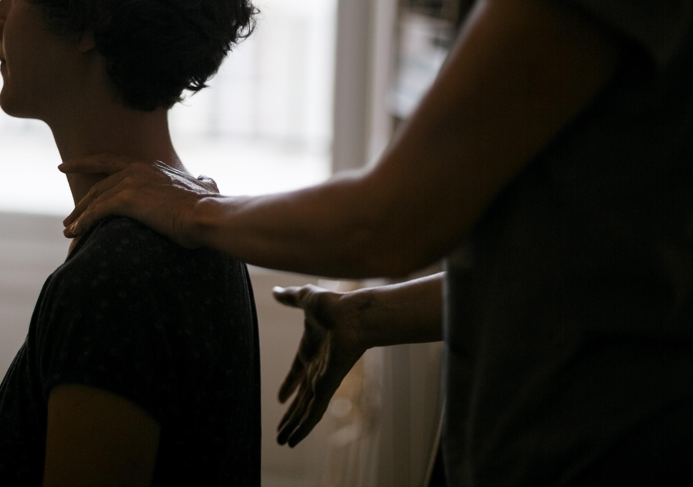 deux mains travaillant doucement la technique alexander sur les épaules d'une jeune femme