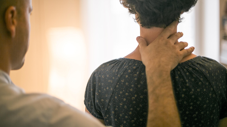 Un thérapeute de la Technique Alexander dont la main droite est posée sur le cou et l'épaule de sa cliente