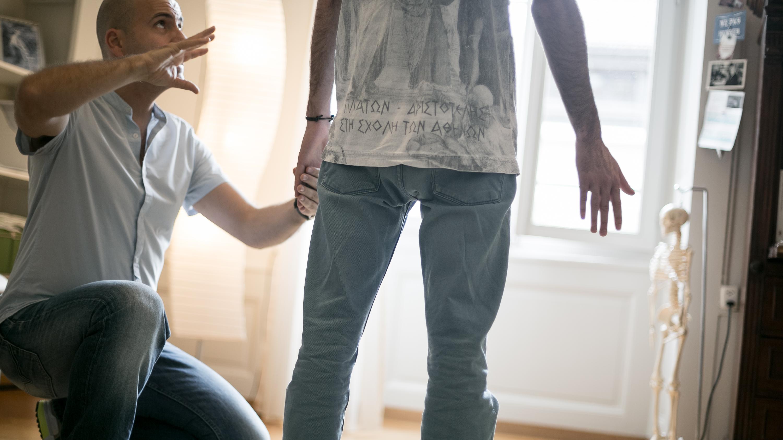 Un thérapeute de la Technique Alexander travaillant avec les bras d'un jeune homme debout